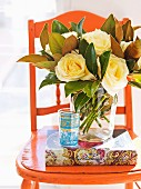 Magnificent bouquet of roses in a glass vase on a vintage chair