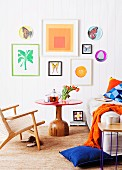 Unusual red table with solid wooden base in bright bedroom with colourful collection of artworks on wall