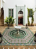 Courtyard with Oriental, tiled fountain; Moorish arch door and staircase in background