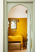 View through Moorish arch door of yellow-painted washing area with masonry sink and Oriental decor