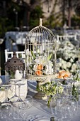 Floral arrangement in bird cage on wedding table in garden