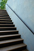 Staircase with handrail on blue wall