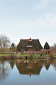 Thatched residential house on a lake (Germany)
