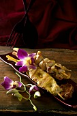 Chicken satay skewers and orchids (Thailand)