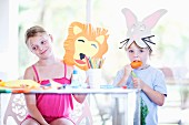 Two children making animal masks from coloured paper