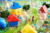 Toy landscape with figurines, houses and marbles