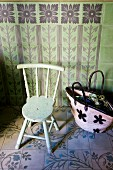 Shopping bag on tiled floor next to old wooden chair against green tiled wall