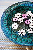 Flowers floating in ornate ceramic bowl in shades of blue