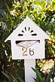 White-painted letter box shaped like a house with house number and white wooden post