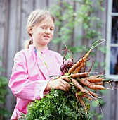 A girl holding carrots, Sweden.