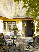 Garden furniture on terrace of thatched, Swedish country house