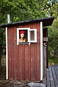 Schwedisches Badehäuschen, lachende Frau mit Handtuchturban am Fenster