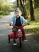Blonde little girl wearing striped hat and gloves riding a tricycle along a woodland path