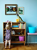 Little girl in front of shelves of toys; animal masks in picture frame and dinosaur figure against wall painted pale blue
