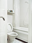 View into simple, white bathroom with translucent, plastic shower curtain in bathtub and raised toilet lid