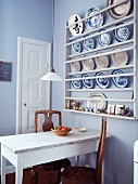 Blue and white crockery and pewter plates in plate rack on lavender-painted kitchen wall; old dining table and antique wooden chairs