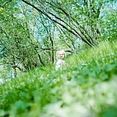 Blonde little girl sitting in grass; trees on tilted horizon