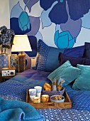 Breakfast tray on double bed in front of decorative, floral wall paper and textiles in many nuances of blue