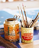 Paintbrushes and scissors in old tins