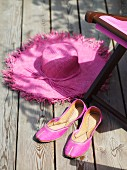 Pink ballerina pumps and straw hat on wooden deck next to deck chair