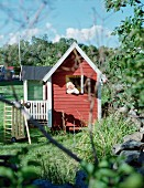 Little girl in wooden Wendy house