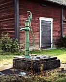 A Water Pump in front of a Barn