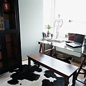 Dunkle Holzbank und Schreibtisch mit Holzböcken auf Kuhfell am Fenster