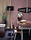 Dining table and chairs below designer pendant lamps against retro wallpaper