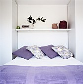 Purple bedspread and scatter cushions on bed with shelf in niche above head