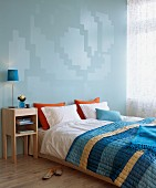 Double bed with striped bedspread and modern bedside cabinet against blue wall