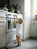 Toddler in babygro standing in front of cooker
