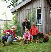 Family in garden with vegetable harvest in front of garden shed