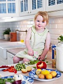 Little girl sitting on kitchen worksurface chopping vegetables