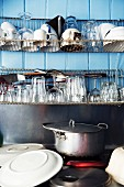 Glasses and cups on metal drying rack above pans on cooker