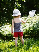 Child hunting butterflies on sunny day in garden