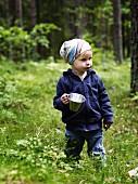 Little girl holding pot in summer forest