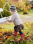 Child playing with swing in autumnal garden