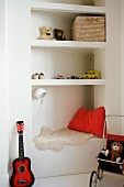 Toys on corner shelving and ukulele in child's bedroom