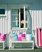 Colourful scatter cushions on bench outside white-painted wooden house on sunny day