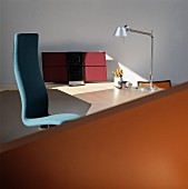 Blue office chair at modern desk with designer table lamp