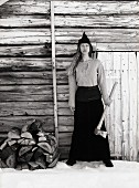 Woman with menacing stare holding axe standing against outside wall of log cabin