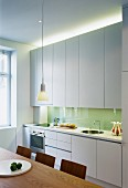 Modern kitchen with white cupboards and indirect lighting