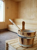 Small wooden tub on wooden bench in home sauna