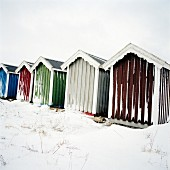Snowy wooden beach huts painted different colours