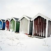 Eingeschneite Holz Strandhäuschen mit verschiedenen farbigem Anstrich