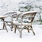 Wicker chairs in snowy garden