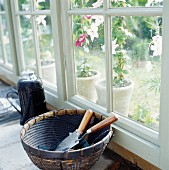 Gardening tools in basket on floor next to French window with view of potted plants outside
