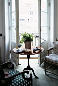 Round, vintage side table and armchairs in front of open balcony door