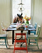 Wooden chairs painted in different colours at set table and curious horse looking in through open window
