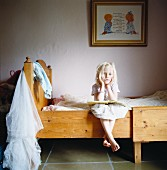 Portrait of a blond girl sitting in a bed, Sweden
